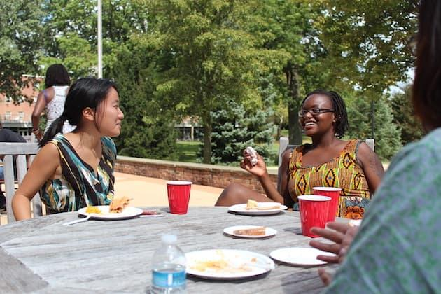Students at a patio table outside the Afrikan Heritage House.