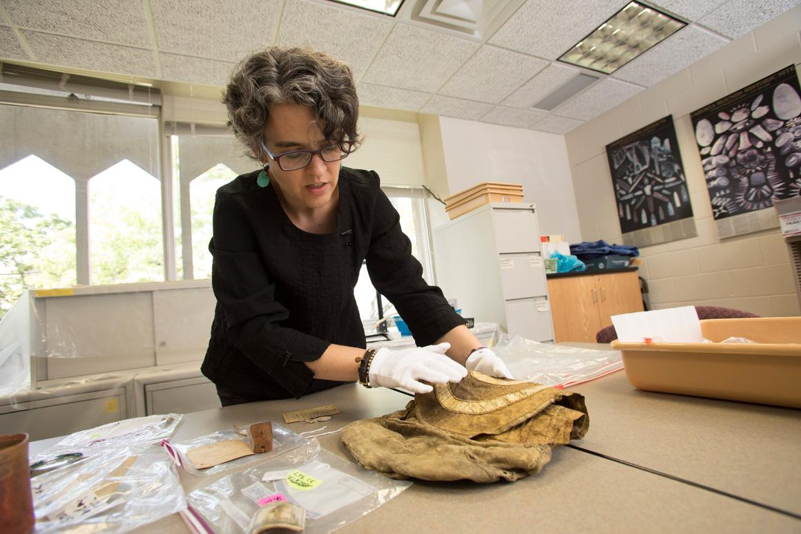 A professor handles an artifact with white gloves.