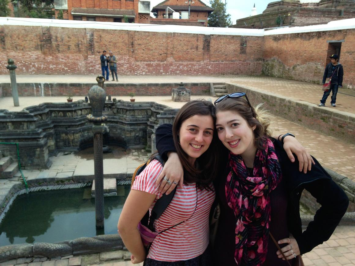 Two people pose at a fountain.