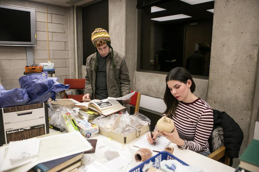 At a table covered with papers, books, and boxes, two students examine an artifact.
