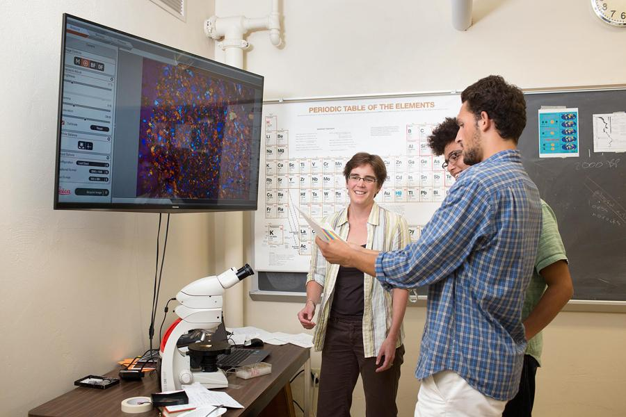 Three people in a lab, where a large screen above a microscope displays a colorful image.