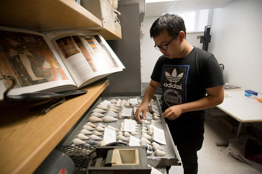 A student works with a tray of artifacts.