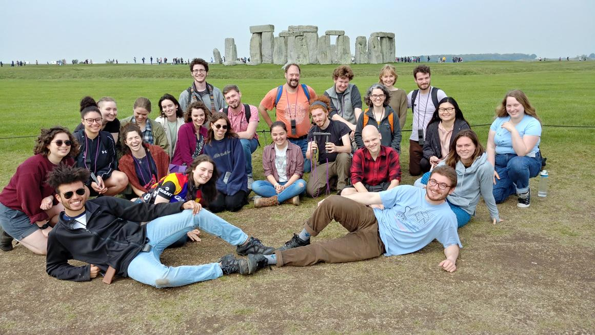 About 2 dozen people pose with the Stonehenge site in the background.