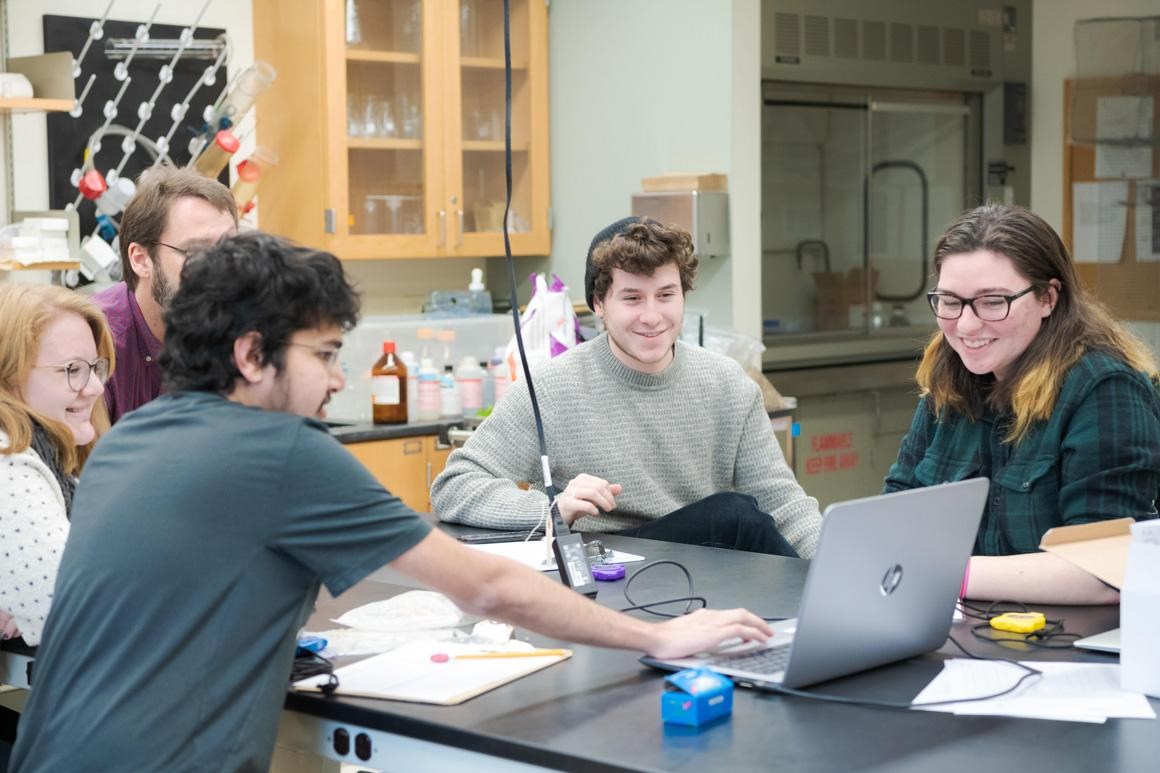 Sitting around a lab bench, students and a professor look at a computer screen together.