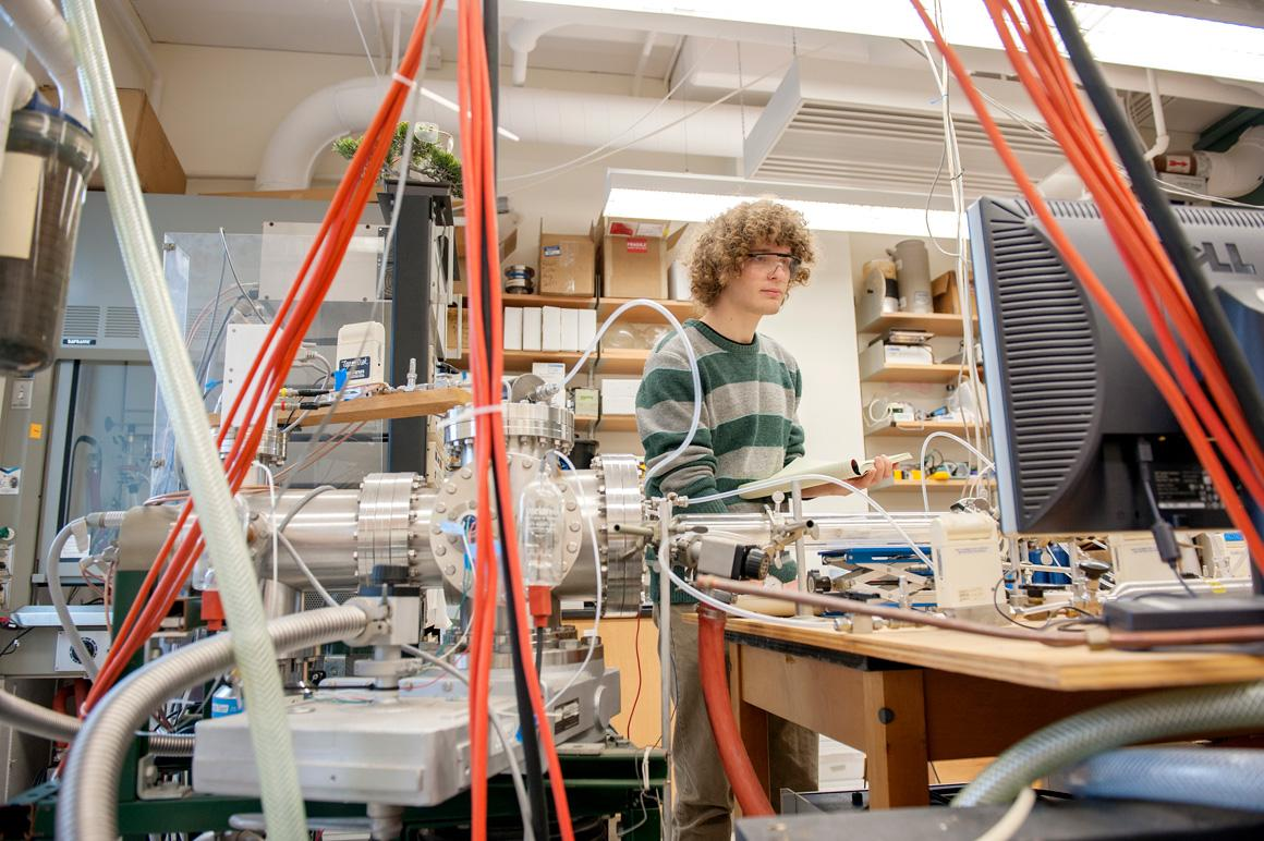 A student surrounded by lab equipment.