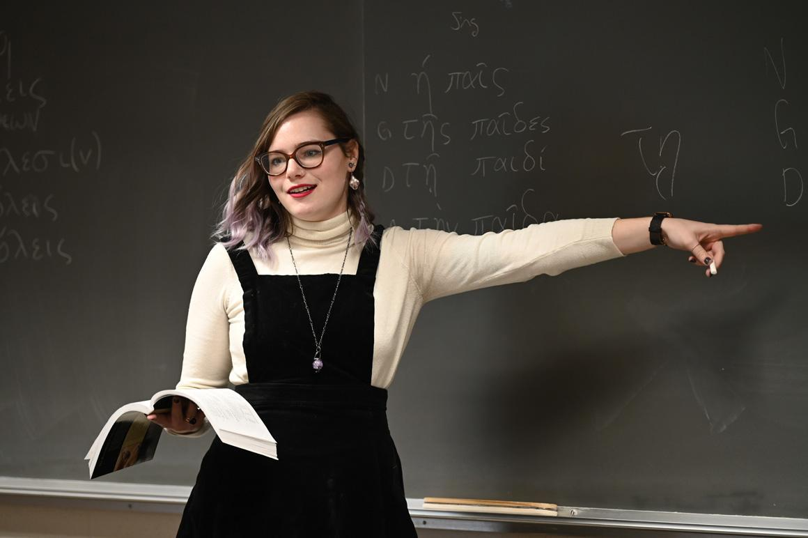 A student holds an open book while pointing something out on the blackboard.