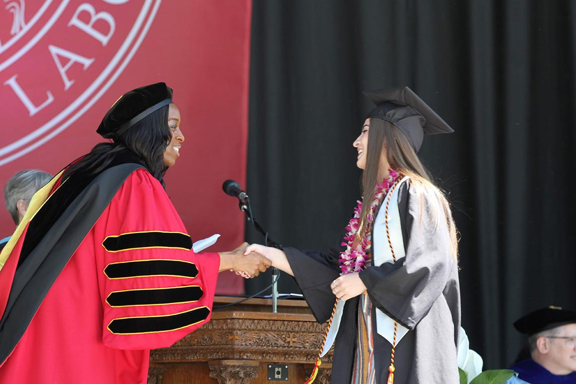 President Ambar shakes a graduate's hand while awarding their degree.