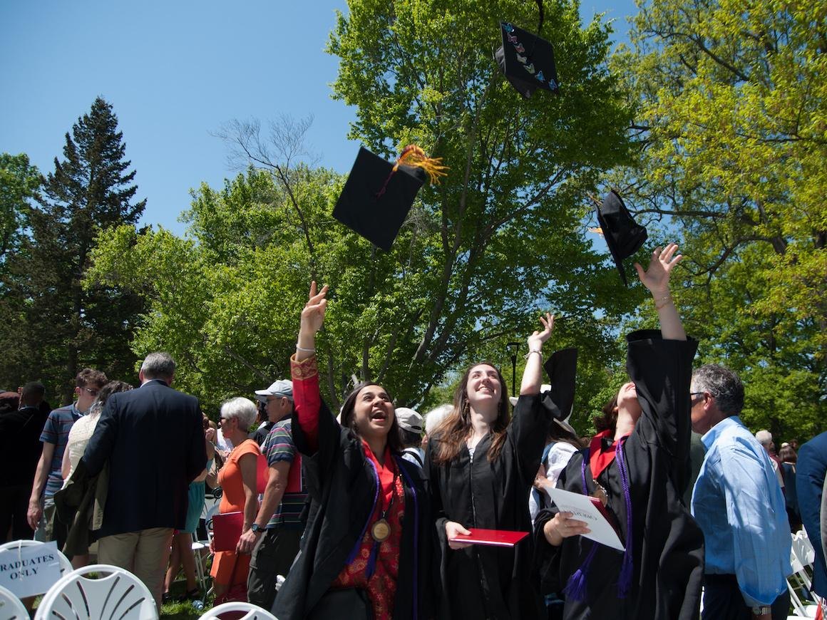 gradutes toss motarboards into the air.
