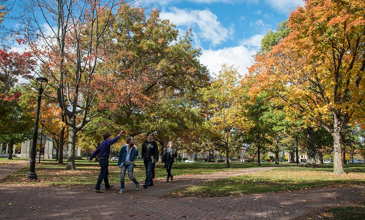A family takes a campus tour amid fall foliage