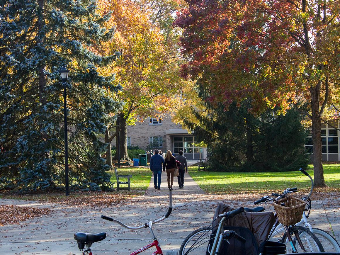 people strolling along campus with bikes in view