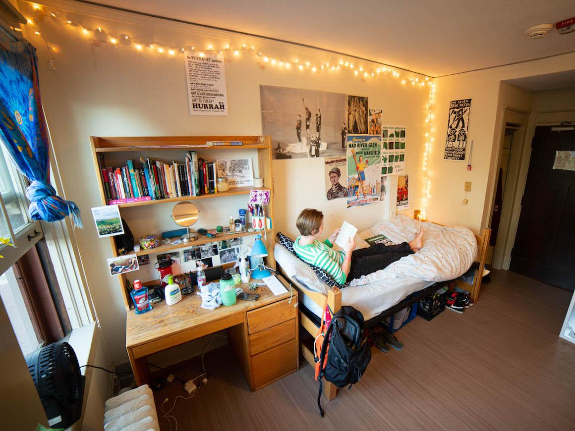 student laying across bed in dorm room.
