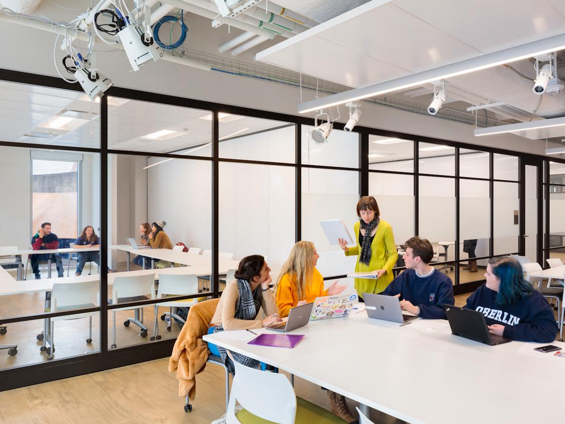 large open classroom setting with professor working with 5 students.