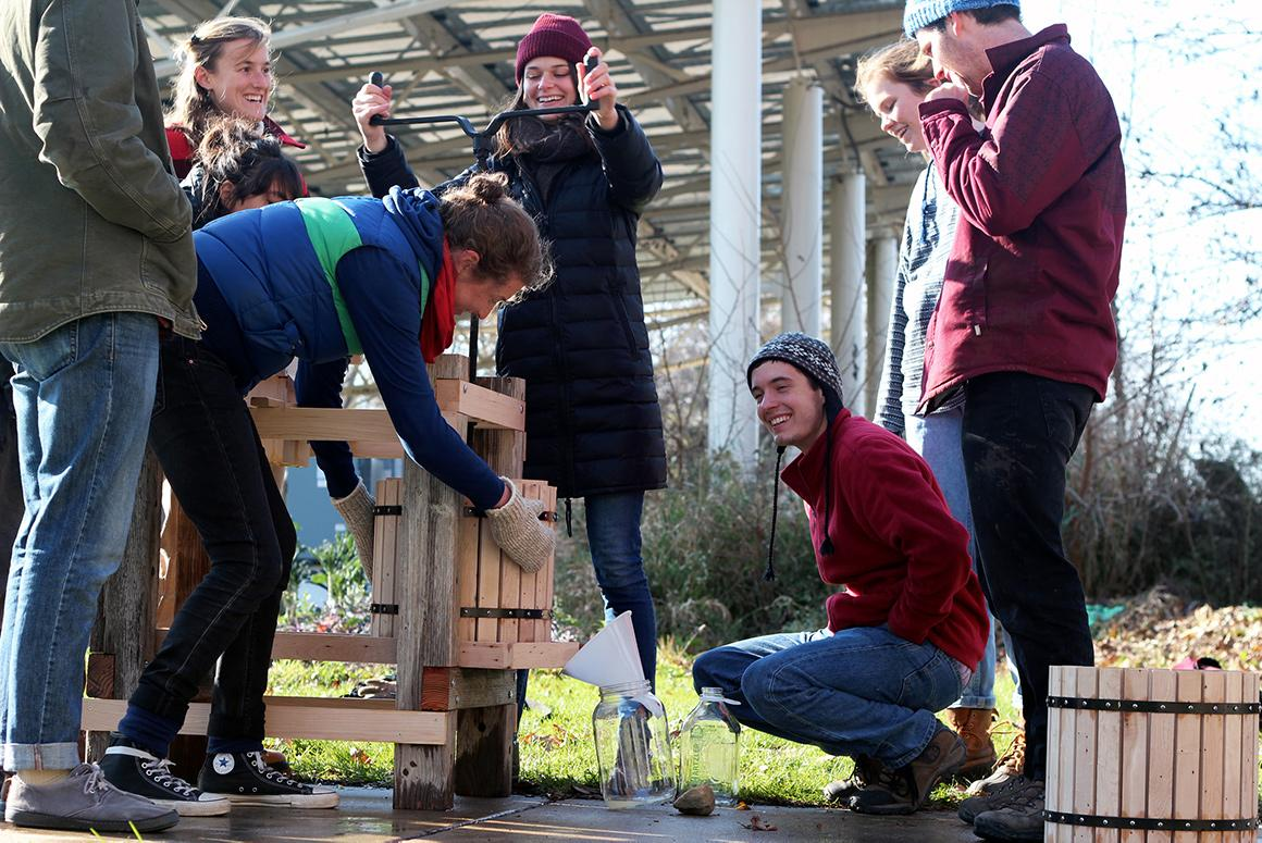 On a cold sunny day, a group of students in winter coats operate an old-fashioned cider press.