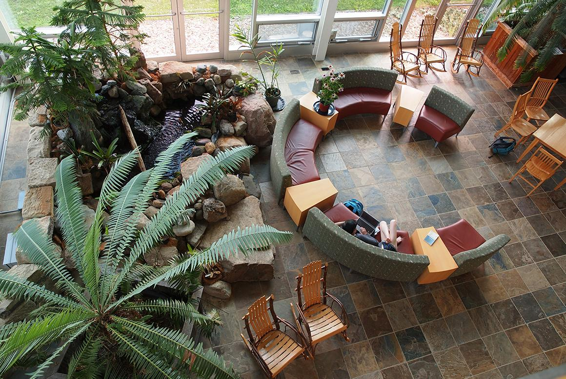 An atrium, viewed from above, features large plants, a rock garden fountain, and modern furniture arranged in a circle.