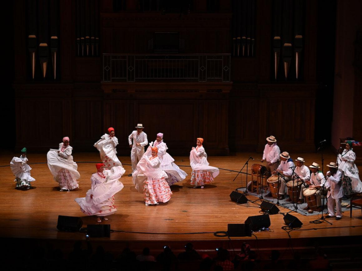 group of latin dancees and musicians perform on stage.