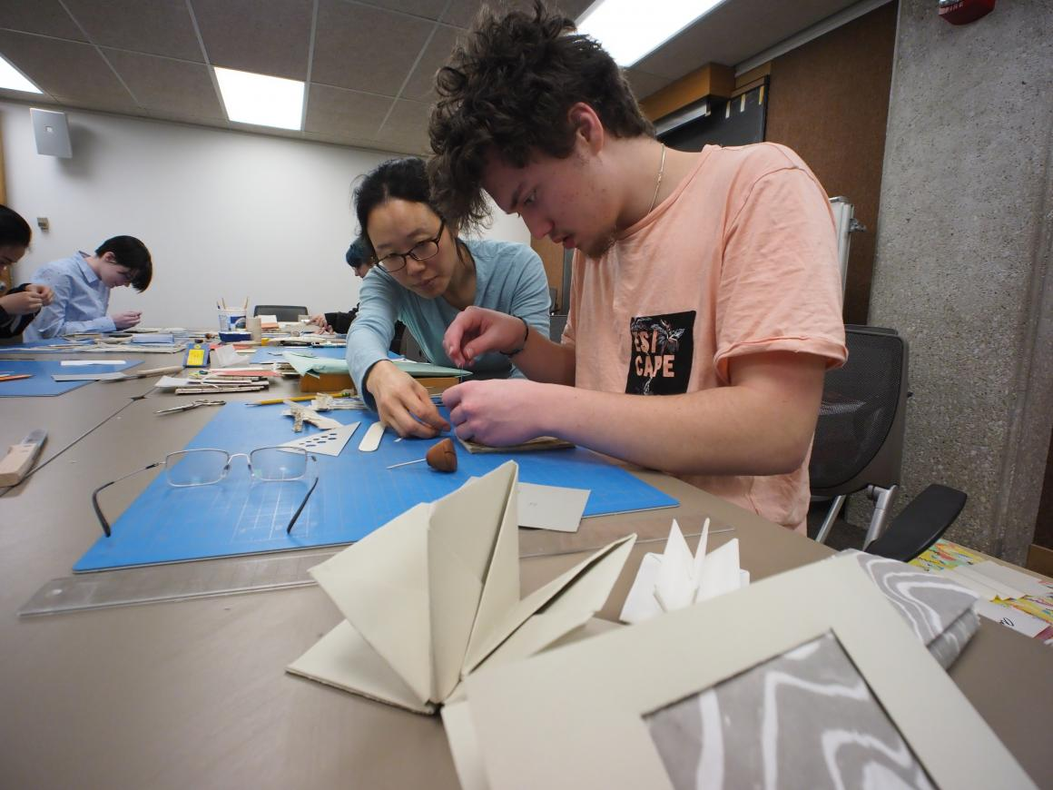 Asian woman showing a student how to cut shapes for bookmaking project.