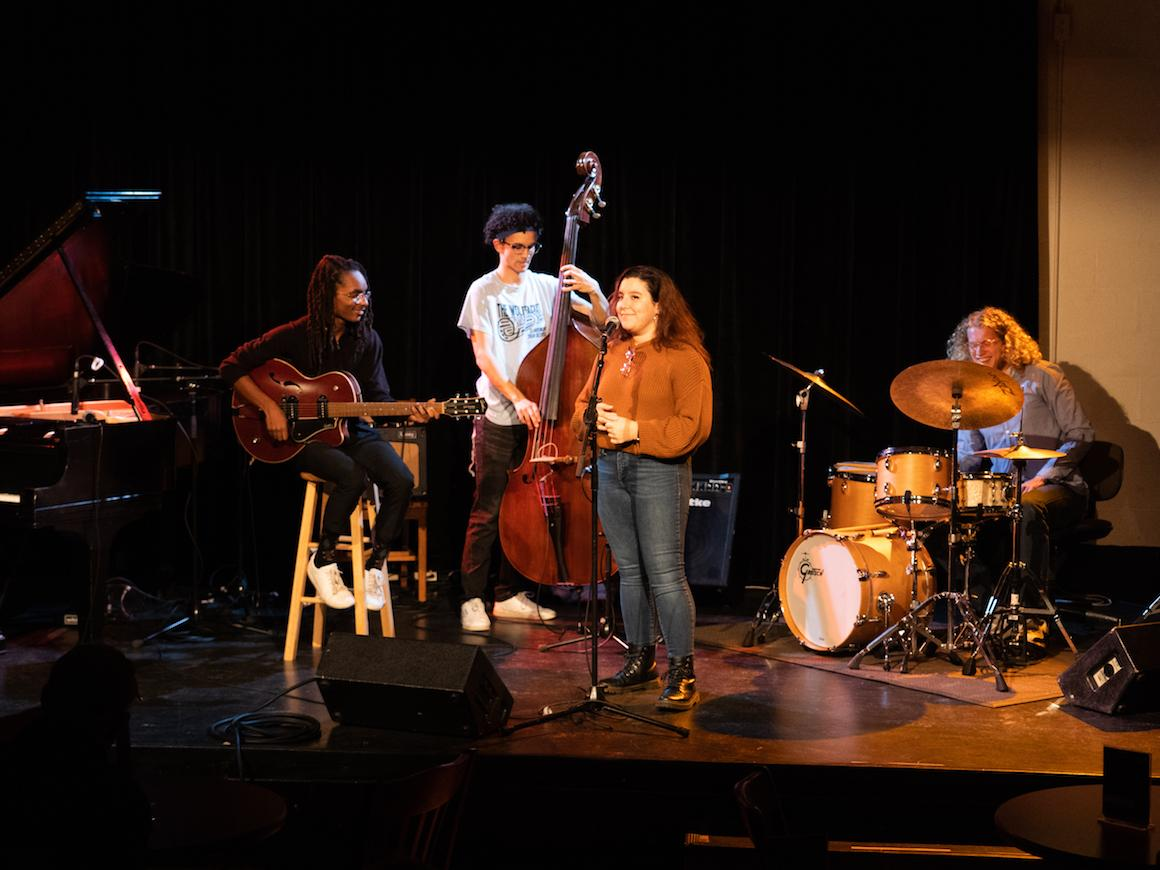 four student musicians on stage preparing to sing and perform on bass, guitar, and drums.