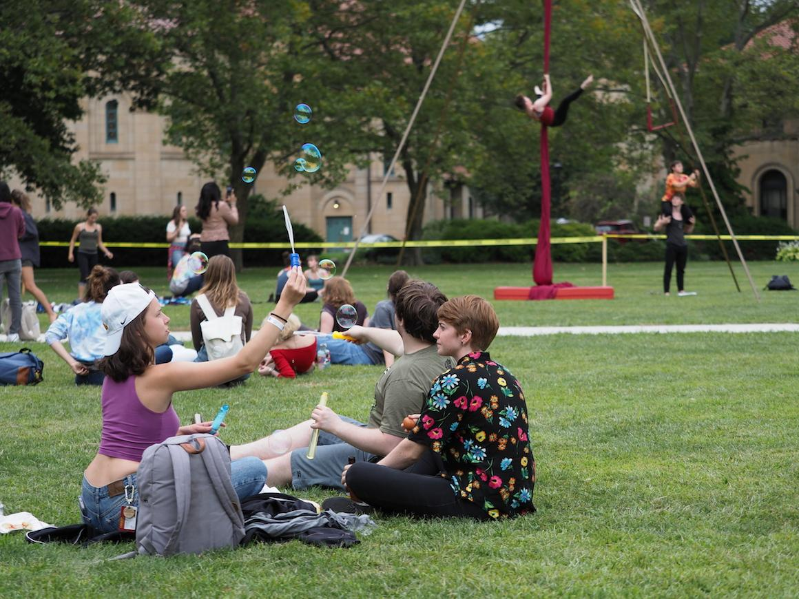 students sitting on grass blowing bubbles or tossing balls.