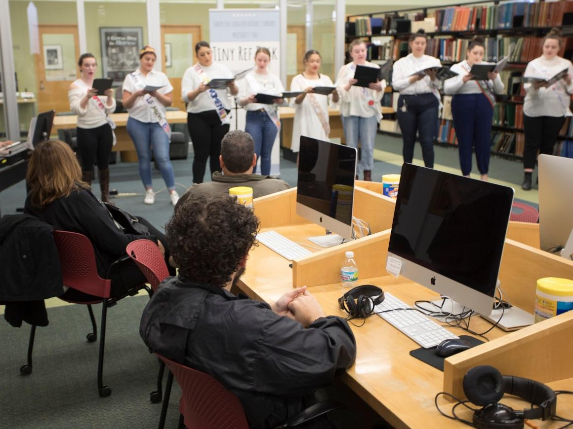 women in a library standing in a row singing a capella while holding music folders.