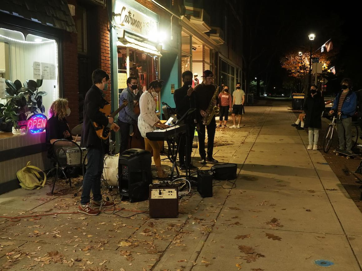 group of students perform jazz outdoors in downtown business area.