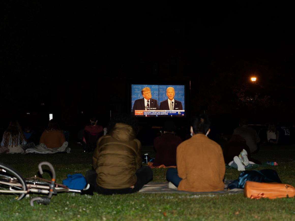 students on outdoors watching big screen tv.