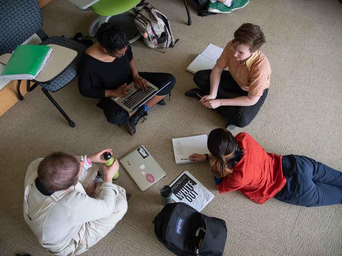 four students seated in circle on classroom floor
