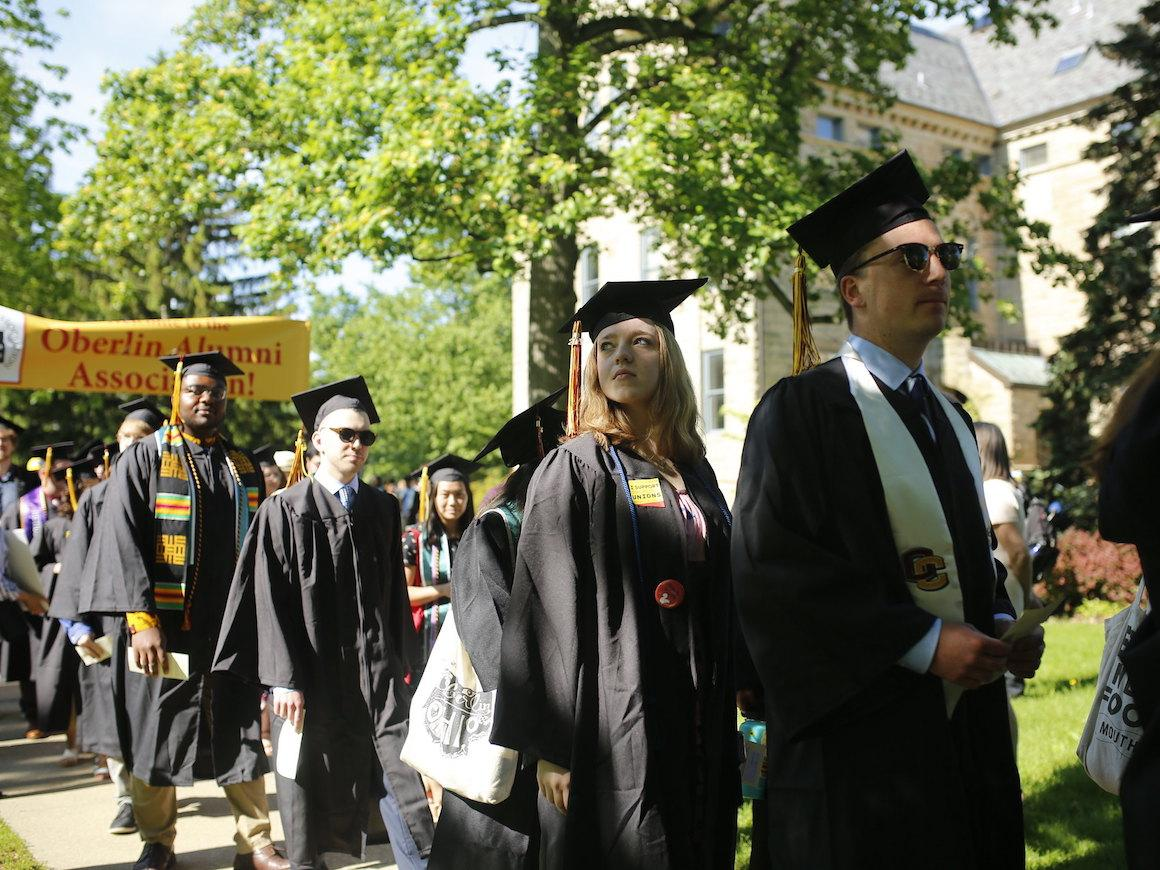 students in grad robes walking in line to stage.
