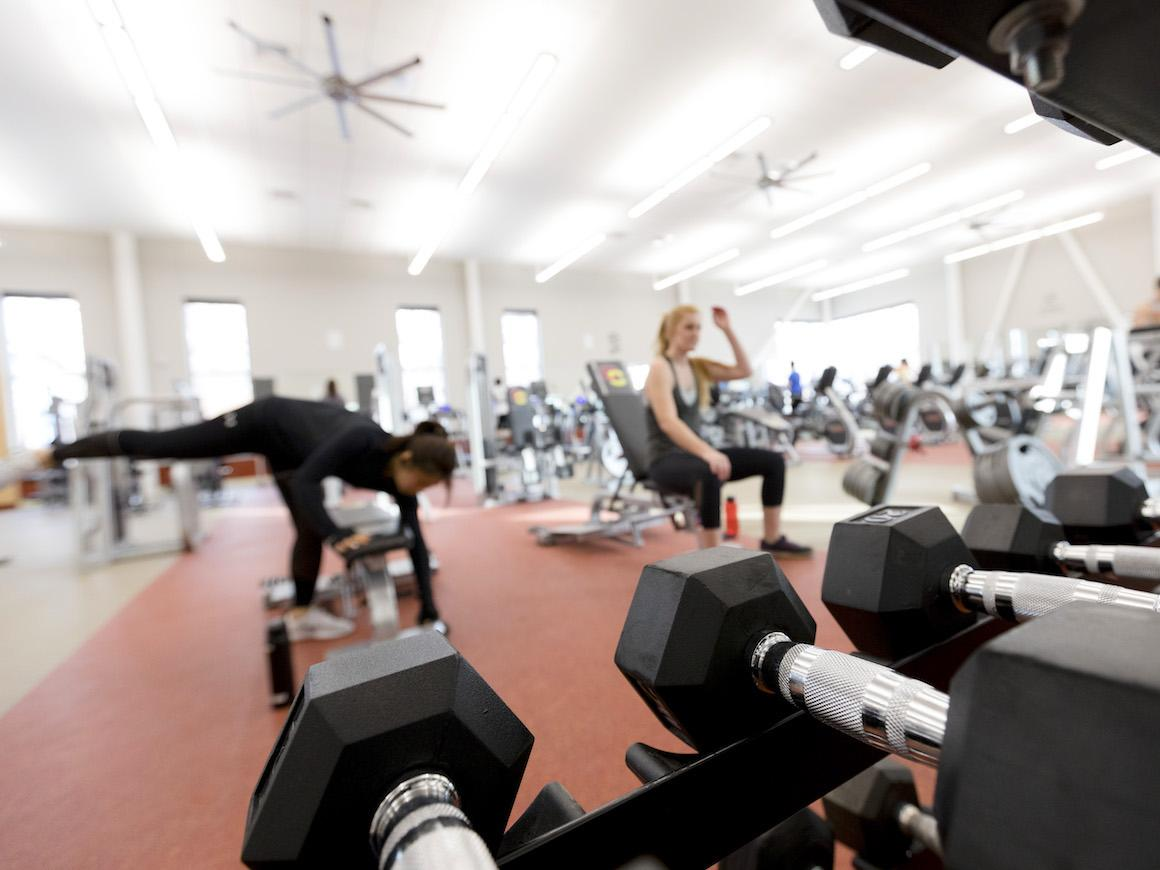 two female students lifting weights in the weight room