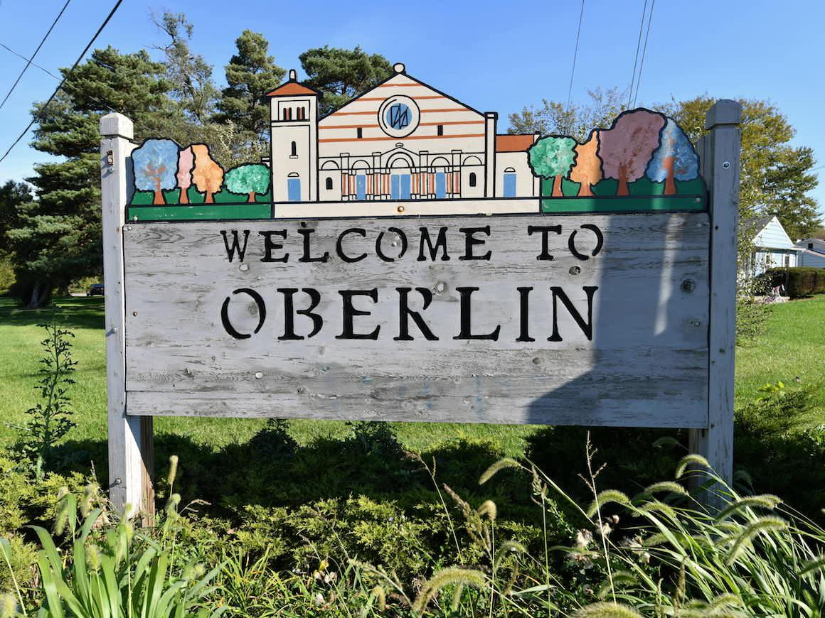 wooden sign with painted letters stating welcome to oberlin.