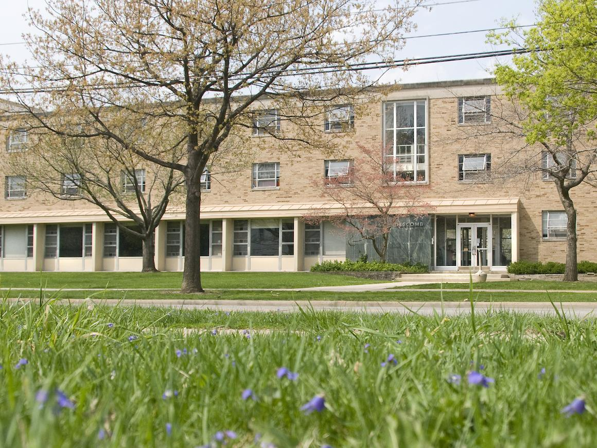 front exterior Dascomb Hall with line of trees and grass in front.