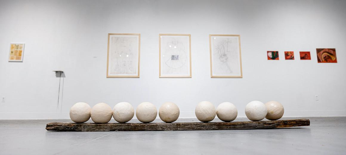 Three framed sketches and a long row of large balls on top of a long wooden plank in an art exhibit.