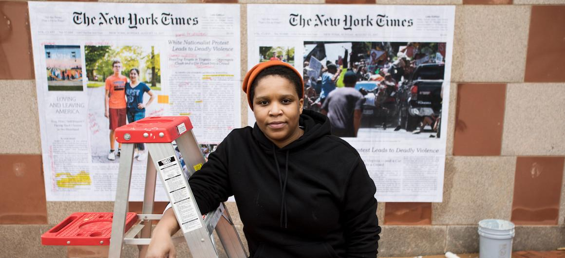 A women standing in front of New York Times newspapers that are pasted onto the side of a building.