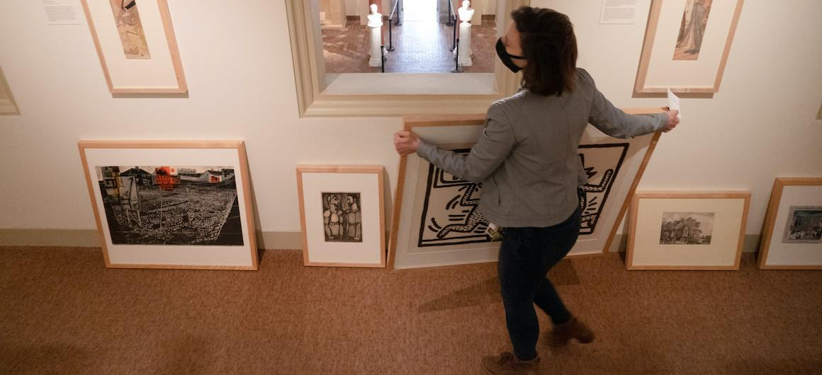 A person carries a large framed print.