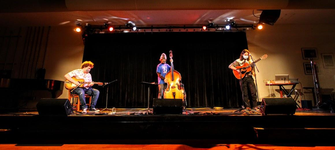 Three musicians perform on a stage.