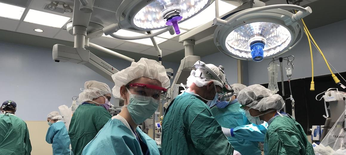 Oberlin student in a surgery room with other doctors.