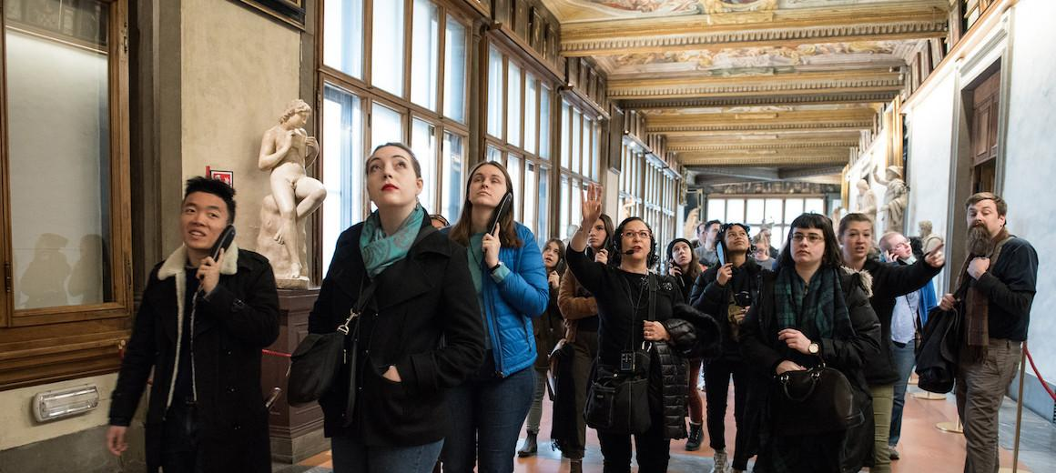 Oberlin students looking up while walking down an ornate hallway in a museum in Italy.