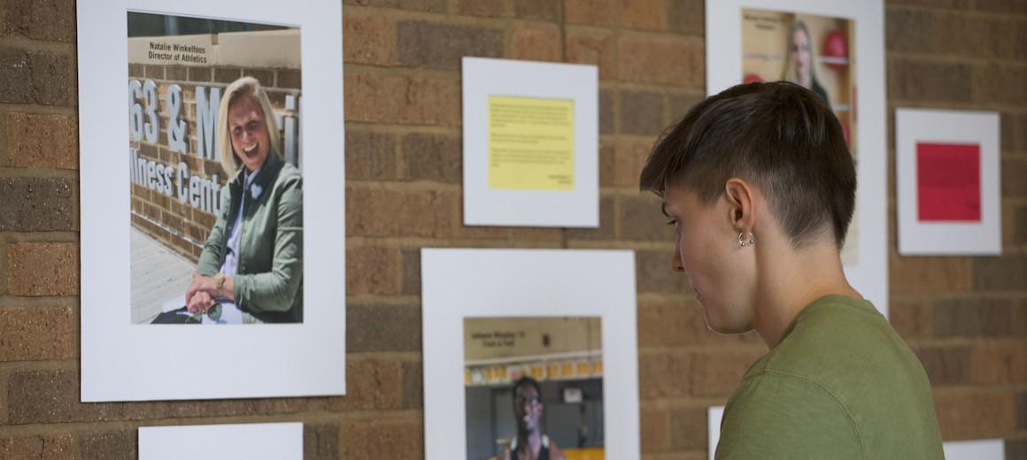 A student looks at pictures in an exhibit.