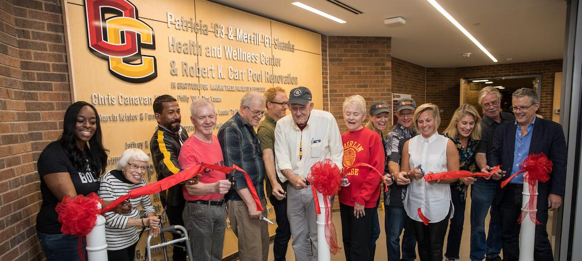 A group of about 8 people--alumni, Oberlin president, and staff--stand in front of a ribbon in the new Health and Wellness Center.