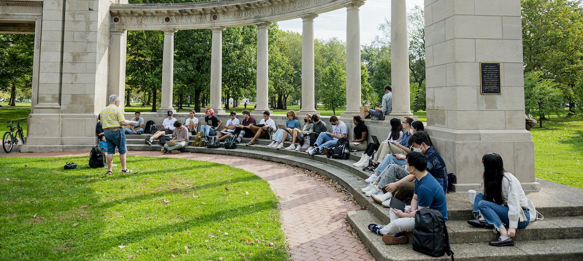 A large class meets at a memorial arch outside.