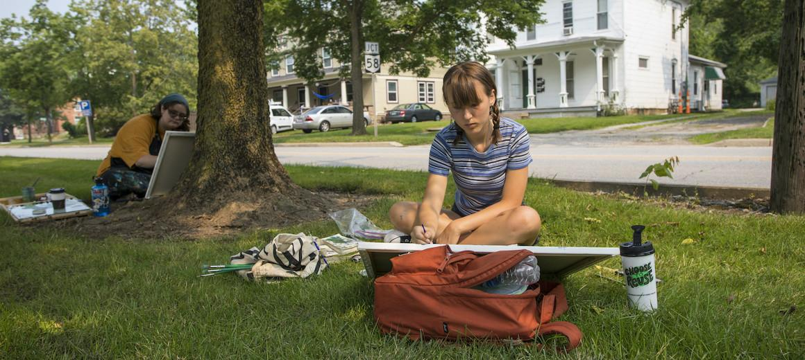 Two students paint on canvas while sitting on a tree lawn.