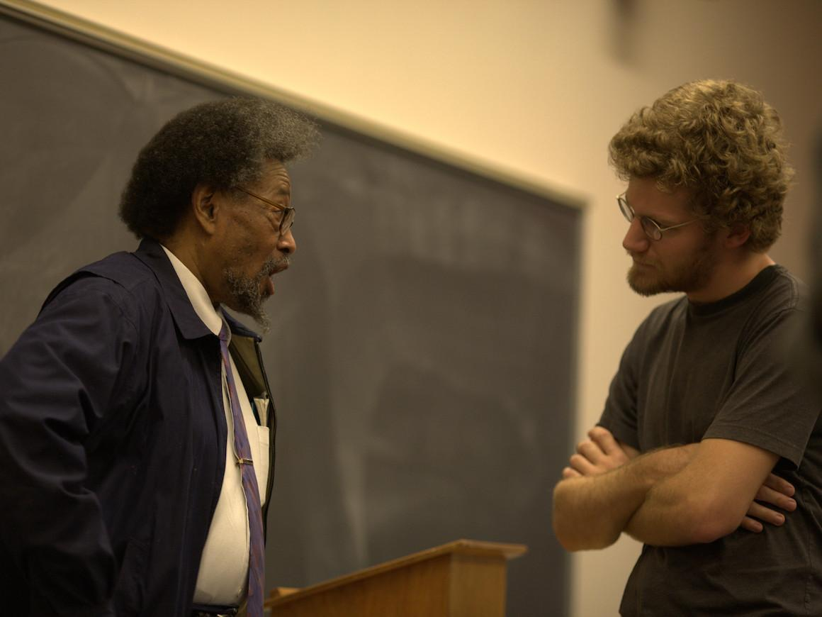 a professor and a student facing each other talking