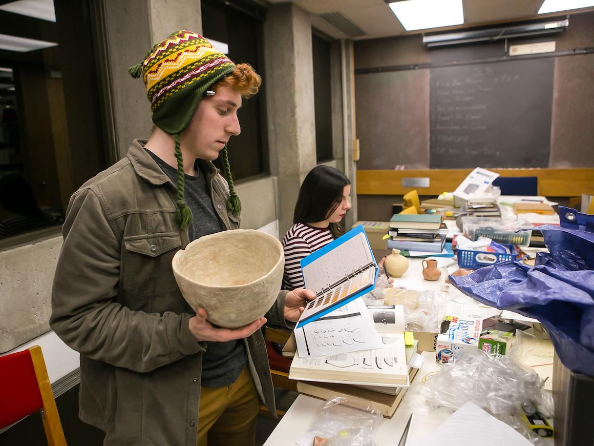 two students discussing material in archeology lab