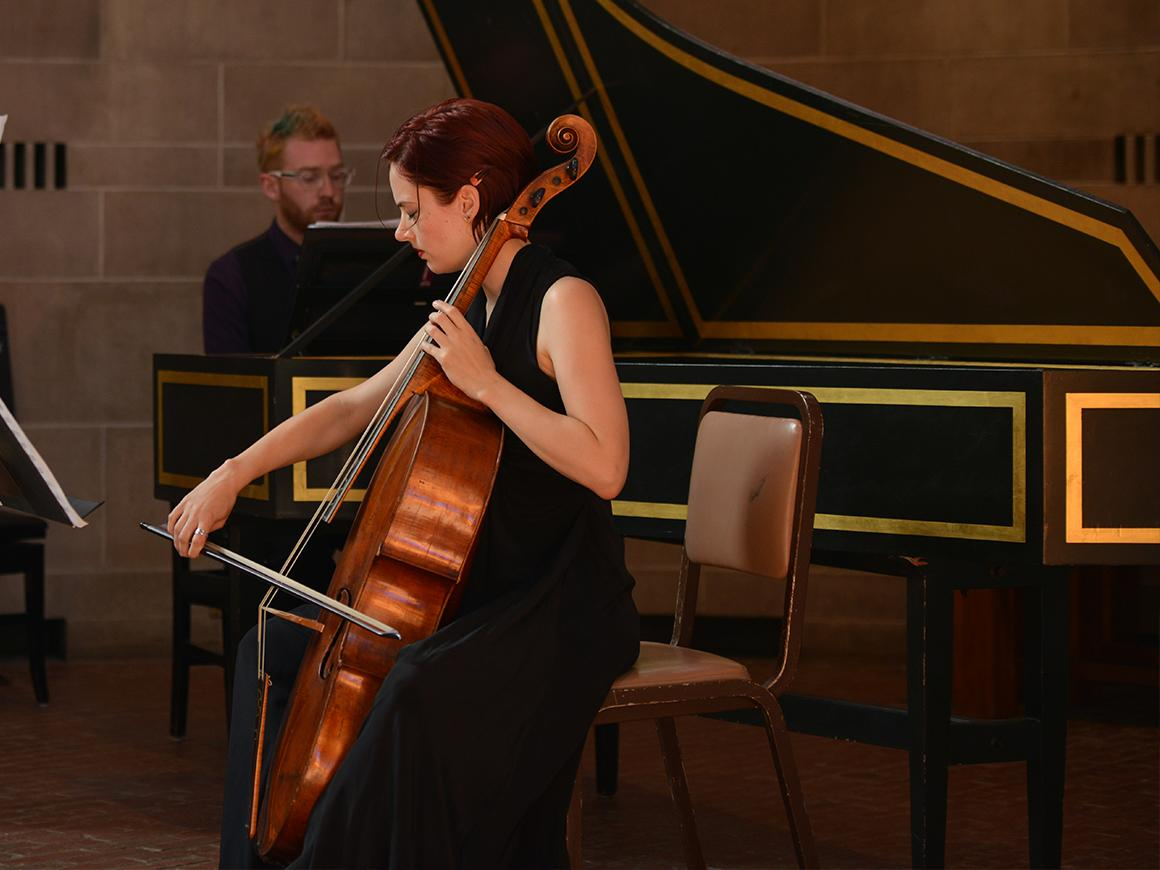 Baroque cellist performing with harpsichordist