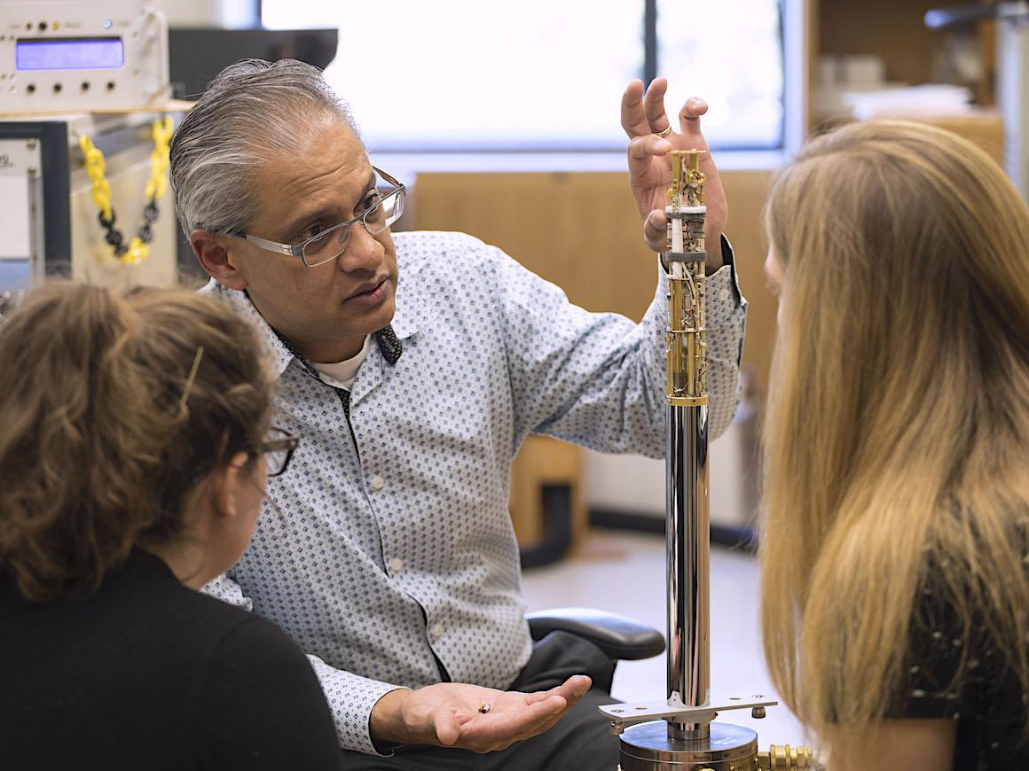 professor shows chemistry equipment to two students.