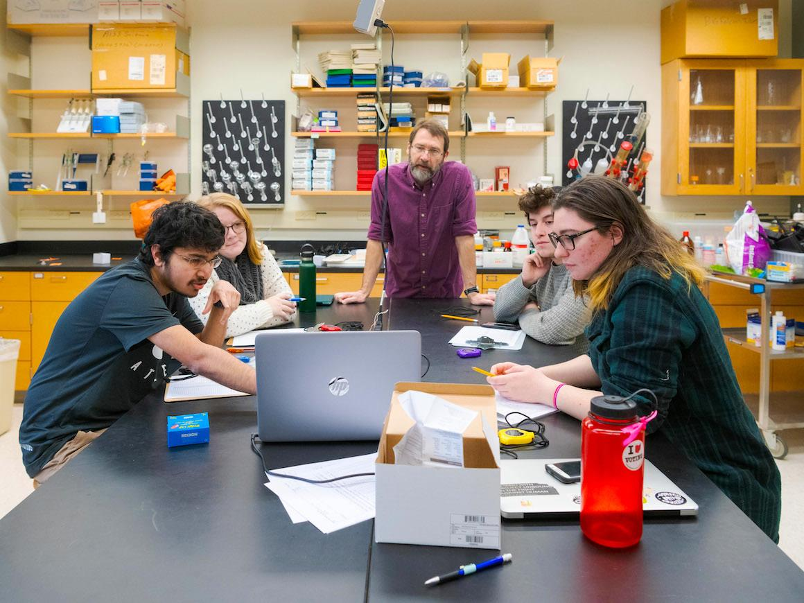 professor and 4 students look at results on a laptop computer.