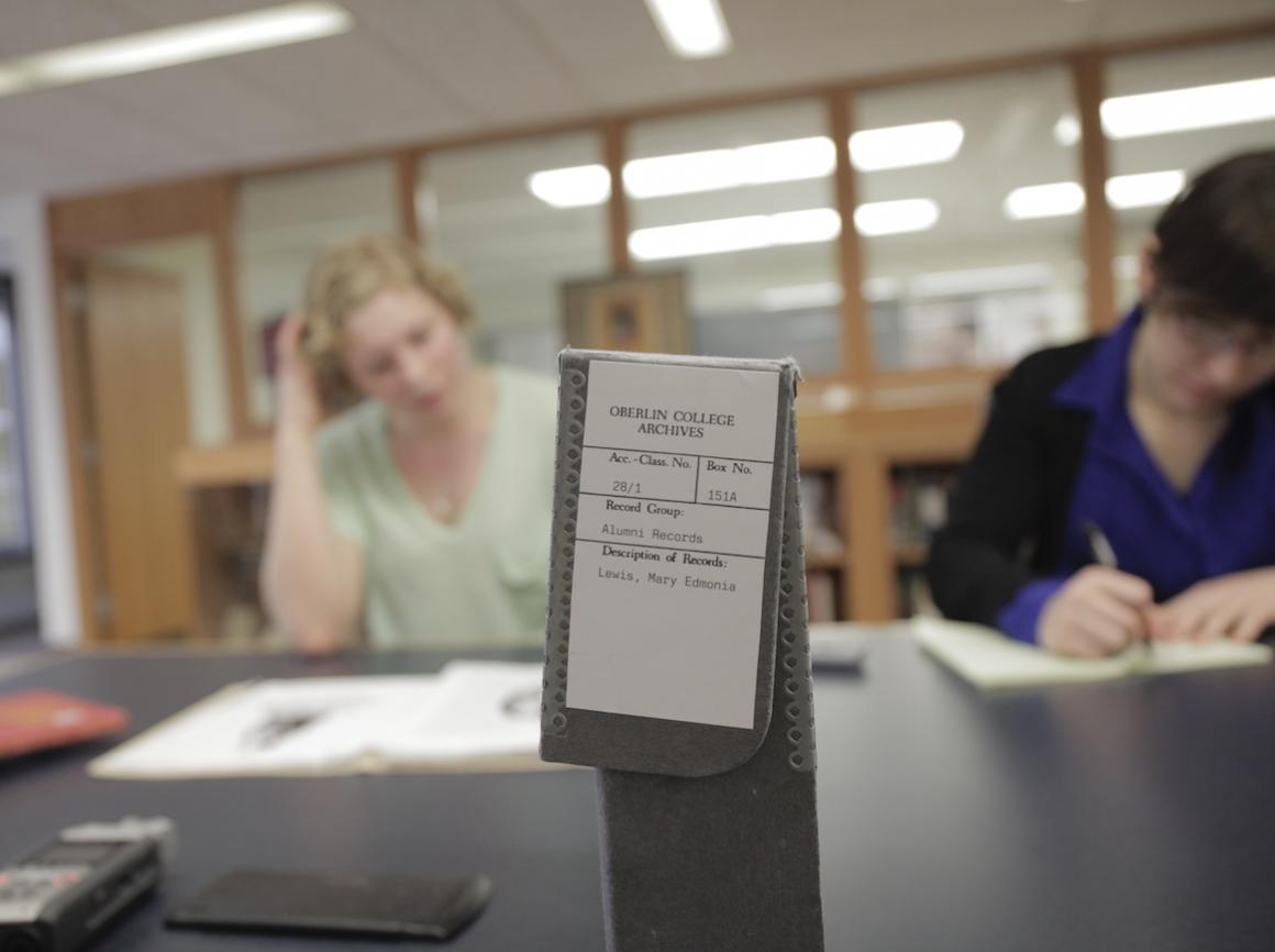 students review books inside a library.