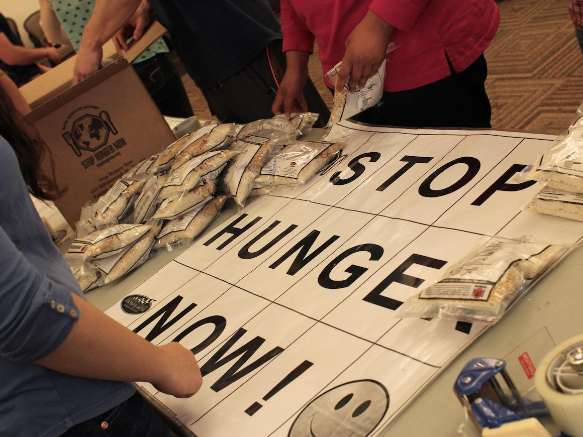 "people designing a banner with the text ""Stop Hunger Now!"""