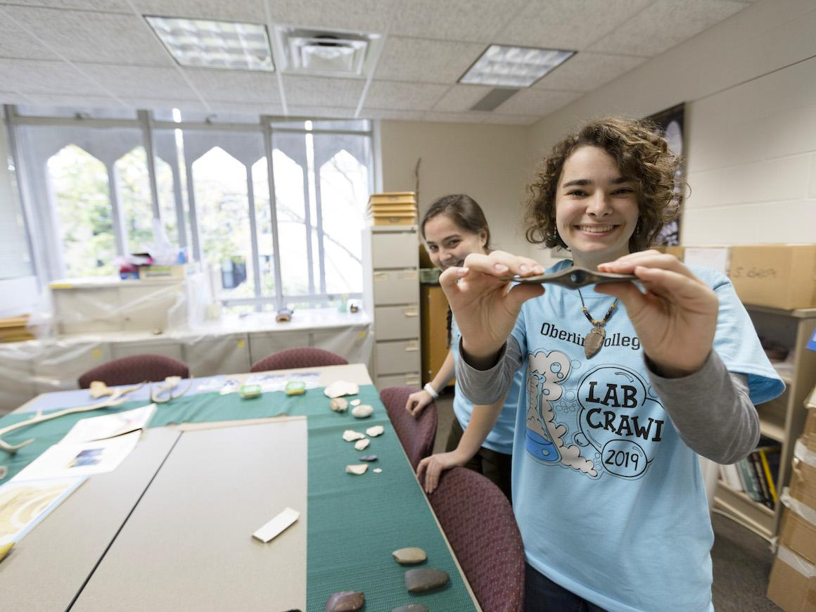 students showing artifacts in an anthropology lab.