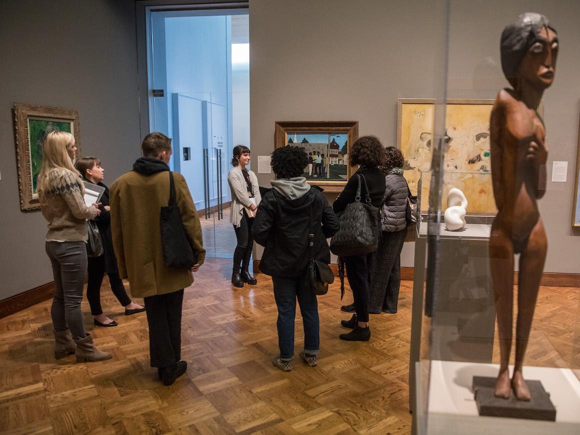 student docent leads a group of people our tour of gallery in art museum.