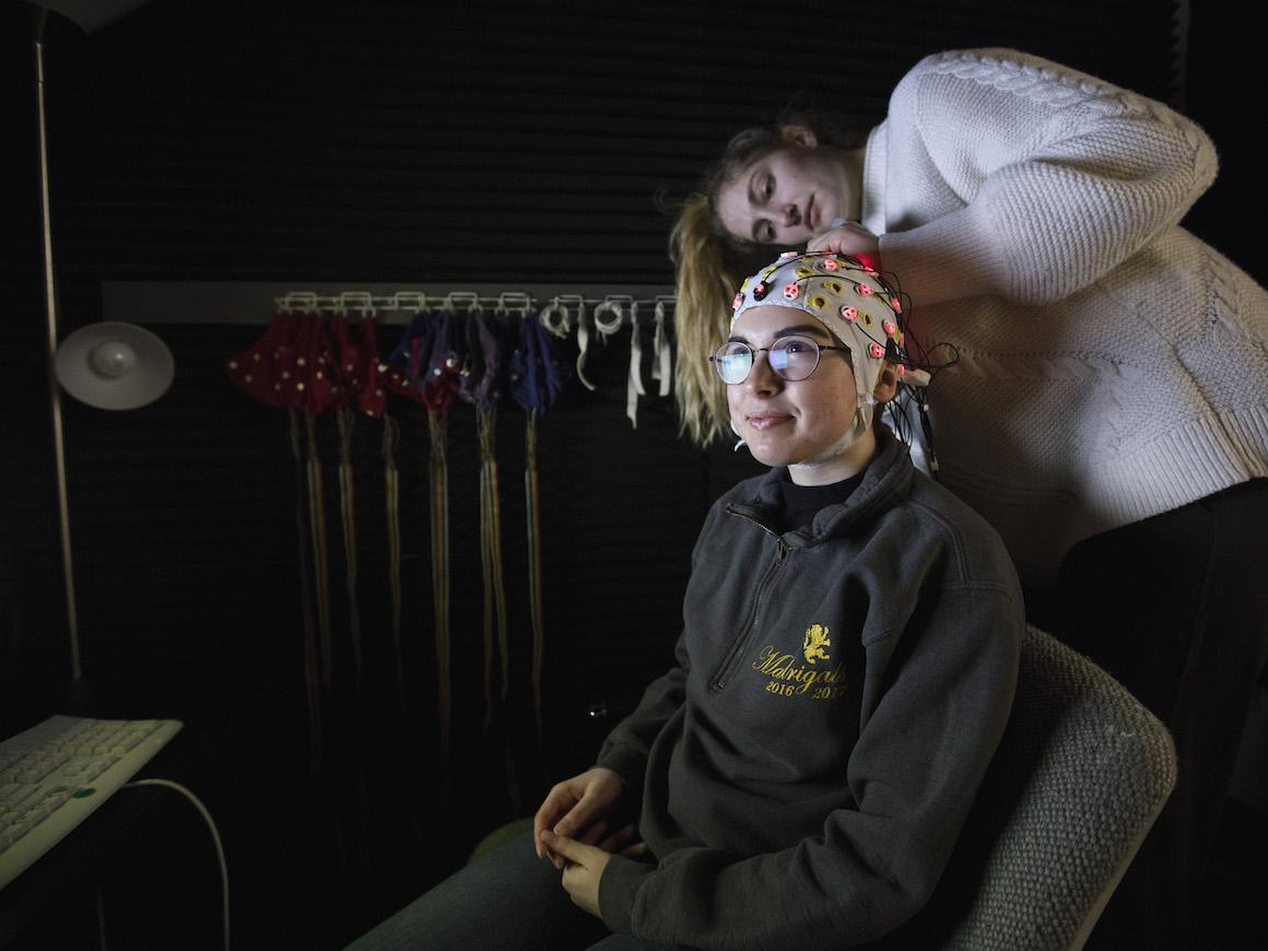 a student adjusts an EEG cap on another student.
